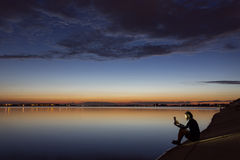 Silhouette of man reading near to lake at sunset.  Royalty Free Stock Photo