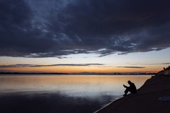 Silhouette of man reading near to lake at sunset Royalty Free Stock Photos