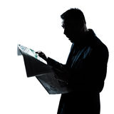 Silhouette man reading newspaper surprised Stock Images