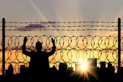 Silhouette of a man refugee. Silhouette of a man near the refugee fence of barbed wire on the background of evening city Royalty Free Stock Photography