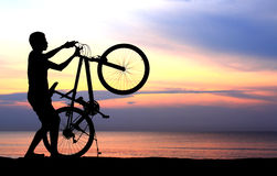 Silhouette of man riding bicycle Stock Image