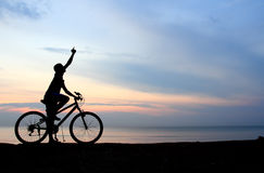 Silhouette of man riding bicycle. With beautiful lake near by at sunset Stock Photos