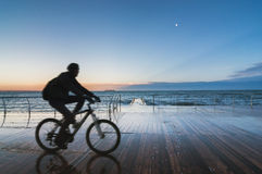 Silhouette of a man riding a bicycle on a pier at sunset Royalty Free Stock Photo