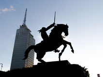 Silhouette of a Man Riding a Horse and Holding a Sword Stock Photography