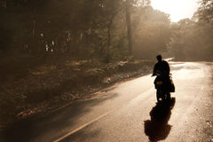 Man riding motorcycle. The silhouette of a man riding a motorcycle by a turning road after a rain stock photo