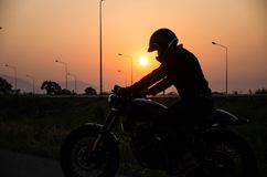Silhouette of man riding vintage motorcycle cafe racer style with helmet stock photography