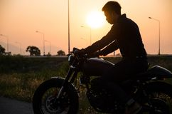 Silhouette of man riding vintage motorcycle cafe racer style. On sunset stock image