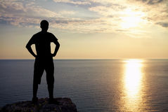 Silhouette of man on rock at sunset. Man on top of mountain. Royalty Free Stock Images