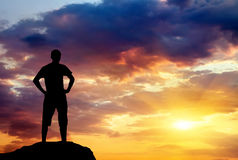 Silhouette of man on rock at sunset. Royalty Free Stock Photo