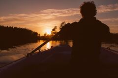 Silhouette of man rowing in sunset