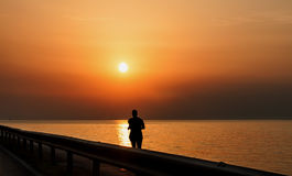 Silhouette of man running along the sea at sunset royalty free stock image