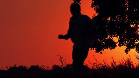 Silhouette of Man Running Through Countryside in Sunset stock footage