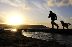 Silhouette Man Running With Dog. Stock Photos