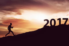 Silhouette man running on the hill toward 2017 Royalty Free Stock Photos