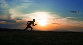 Silhouette man running on meadow stock photos