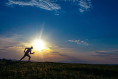 Silhouette man running on meadow Stock Images