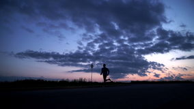 Silhouette of a man running on the road at sunset