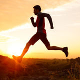 Silhouette of Man Running on the Rocky Trail at Sunset. Extreme Sports. Royalty Free Stock Images