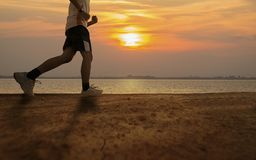 Silhouette of man running with sunrise or sunset background. Beside the lake Stock Image