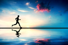 Silhouette of man running at sunset. Water reflection Royalty Free Stock Photo