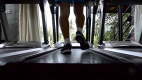 Silhouette of man running on treadmill. At gym stock video