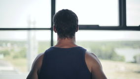 Silhouette of man running on the treadmill and looking into the large window. Close up stock video