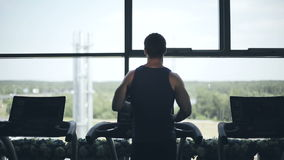 Silhouette of man running on the treadmill and looking into the large window. Left to right dolly shot stock footage