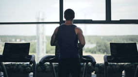 Silhouette of man running on the treadmill and looking into the large window. Medium distance of shot stock footage