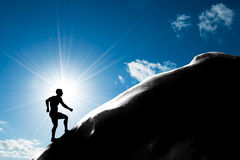 Silhouette of a man running up hill to the peak of the mountain. Trekking, active lifestyle, motivation, strength