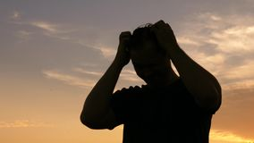 Silhouette of man is scratching his head against the sky