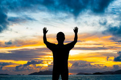 Silhouette man show two hands up in the air. At sunset beach Royalty Free Stock Photography