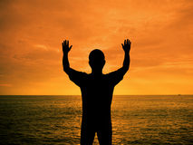 Silhouette man show two hands up in the air. At sunset beach Stock Image