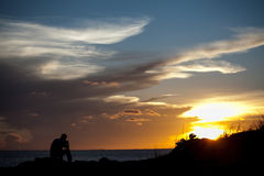 The silhouette man sits on a cliff Stock Photo
