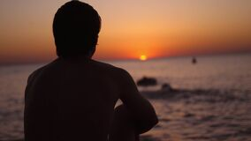 Silhouette of a man sitting alone on the beach looks sunset. Lonely, thinking person.