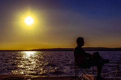 Silhouette of man sitting on the beach and fishing. Silhouette of man sitting on the beach at sunset and fishing Royalty Free Stock Image