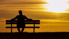 Silhouette man sitting on a bench looking up at the sunset Royalty Free Stock Images