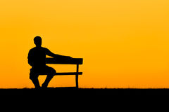 A silhouette of man sitting on bench in sunset Royalty Free Stock Images