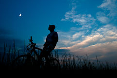 Silhouette of the man sitting on the bicycle Stock Photography