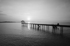 Silhouette of a man sitting on the bridge alone in black and white mode. Stock Photos