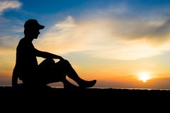Silhouette of a man sitting near the ocean. Bali, Indonesia Royalty Free Stock Photos