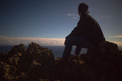 Silhouette of Man Sitting on Rock during Sunset Stock Photography