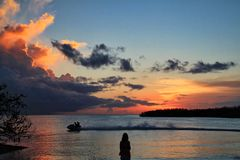 Silhouette of photographer and couple on jetski watching a deep orange sunset over horizon at Sombrero Beach in Marathon Key. Silhouette of man sitting in sand Royalty Free Stock Image