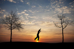 Silhouette of man on slackline Stock Photography
