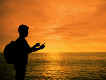 Silhouette man with smartphone in hands at sunset. Beach Royalty Free Stock Photography