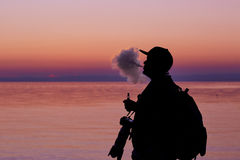 Silhouette of man smoking a pipe in cap at sunset. Photographer Royalty Free Stock Images