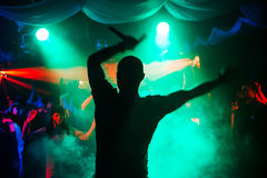Silhouette of a man on stage in a nightclub with a fun dancing crowd. With blurred background bright lasers Stock Photos