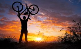Silhouette the man stand in action lifting bicycle above his head royalty free stock photo