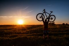 Silhouette of a man with a bicycle stock images
