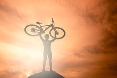 Silhouette the man stand in action lifting bicycle royalty free stock photos