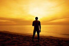 Silhouette of Man stand on the beach at Sunset royalty free stock photography